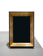 Black space on vertical gold frame on grey desk.