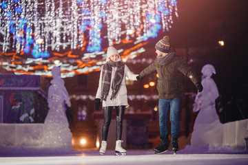 Man and woman skate night on winter skating rink, in background bokeh illumination. Concept training caring love