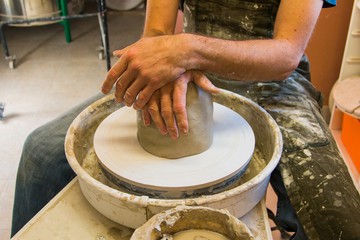 Artist potter in the workshop taking a break from work. Hands closeup. Small artistic craftsmen business concept.