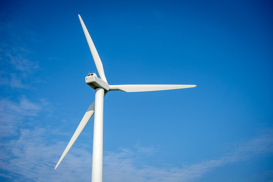 Wind turbine over the blue sky. A wind turbine, or alternatively referred to as a wind energy converter, is a device that converts the wind's kinetic energy into electrical energy.
