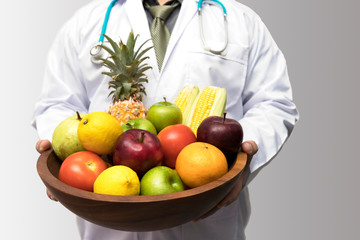 Doctor holding basket assort fresh fruits and vegetables isolated on white background.