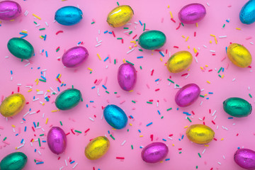 Easter eggs in colorful foil and sprinkles over pink, festive background