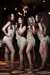 Beautiful women singing karaoke songs in microphones in restaurant