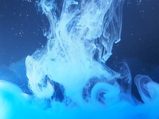 Blue paint is mixed with water. The dissolution of ink in water.