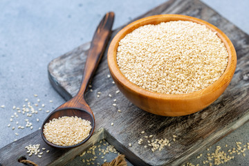 White sesame seeds in a wooden bowl and spoon.