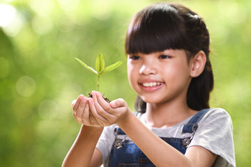 A girl holding a young plant in her hands with a hope of good environment, selective focus on plant