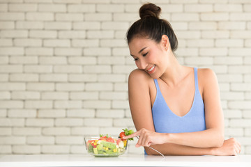Asian woman in joyful postures with salad bowl on the side