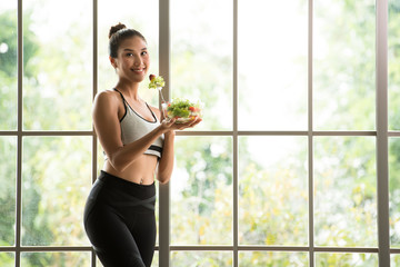 Healthy Asian woman standing and holding a salad bowl looking relaxed and comfortable