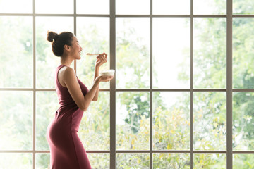 Healthy Asian woman standing and holding a bowl of yogurt looking relaxed and comfortable