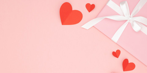 Valentine day idea composition: pink gift box with white ribbon and small red hearts on paper coral background. Top view. Love day concept flat lay