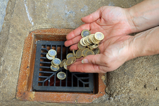 pair of hands tipping money coins down the drain