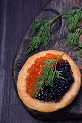 Red and black caviar in a tartlet garnished with dill