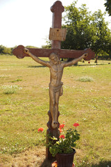 Wayside wooden cross with the figure of the crucified Christ.