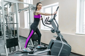 Young fitness woman exercising in modern sport gym. Fitness, sport, training, people concept