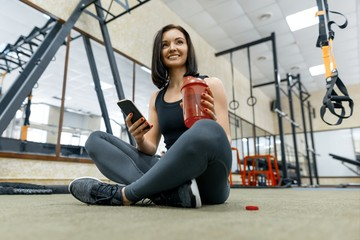 Young healthy woman with bottle water resting in the gym after fitness, woman smiling sitting on the floor. Fitness, sport, training, people, healthy lifestyle concept