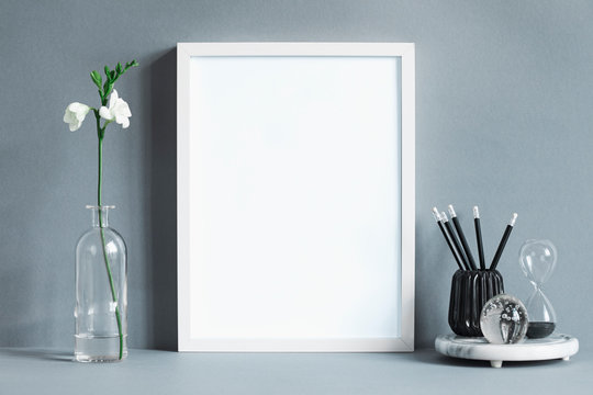 Minimalistic composition of mock up photo frame with flower leaf in vase, office accessories and glass ball.  Stylish concept of mockup frame on gray background wall.