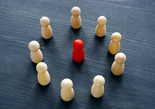 Circle from wooden figures and red figure. Discrimination or harassment concept.