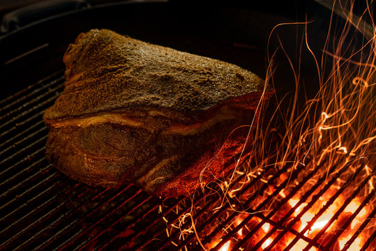 Juicy Smoked Pork Shoulder on Barbeque Grill with Sparks