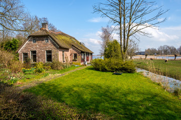 Early spring view on Giethoorn, Netherlands, a traditional Dutch village with canals and rustic thatched roof farm house.