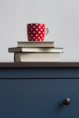 stack of closed books with tea cup on top on blue chest of drawers