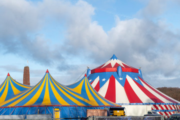 Red and white circus tent topped with bleu starred cover against a sunny blue sky with clouds