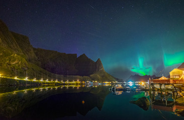Northern lights Aurora Borealis over illuminated fishing village of reine lofoten islands.