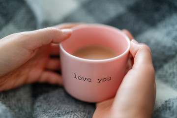 Winter warm coffee cup woman relaxing at home cozy with wool blanket - morning breakfast girl drinking with the words LOVE YOU written on pink mug for valentines day. Romantic quote.