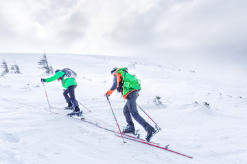 Two ski sportsmen going up to the  summit in snowy mountains. Skitouring sport concept.