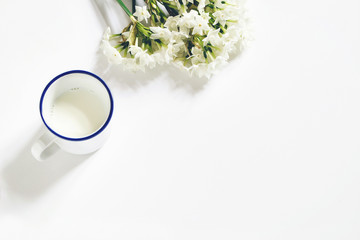 Breakfast scene. Spring composition with mug of milk and bouquet of narcissus, daffodil flowers on white wooden table background. Easter concept. Flat lay, top view. Styled stock image.