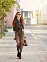 Fashion portrait of beautiful woman walking on a street - full length