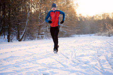 Photo of running athlete among trees in winter forest