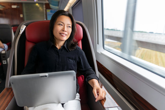 Business trip Asian woman working on laptop on train commute travel lifestyle. Middle aged chinese businesswoman smiling looking out window in contemplation.