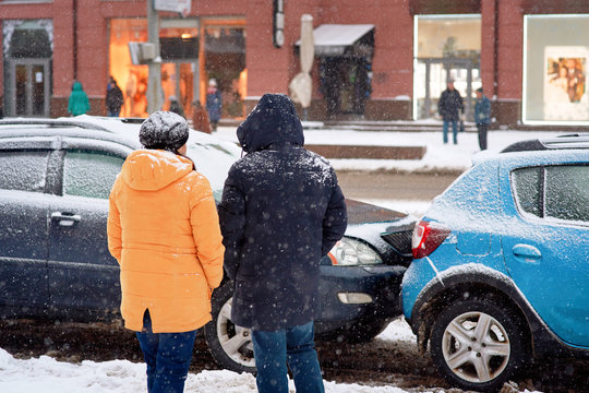 Drivers look at damaged cars after road accident in blizzard. Car crash accident on winter road with snow, safe distance when driving on slippery roads. Winter driving - car breakdown.