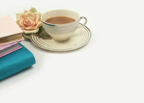 notebooks and diary with rose flower next to cup of coffee or tea on clean white office desk table. ready for adding text