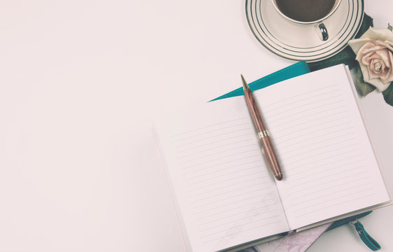 Top view image of open notebook with blank pages next to rose and cup of coffee on clean office desk. For adding text or mockup. pink overlay tone