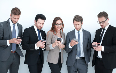 group of business people looking at the screens of their smartphones