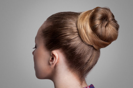 Profile side view closeup portrait of woman with creative elegant brown collected hairstyle, bun hair. indoor studio shot, isolated on grey background.