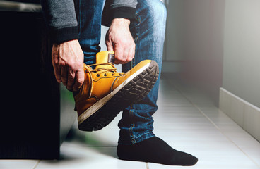 Putting shoes in the hall, preparing for the exit. The man puts on a foot a brown shoe. The concept of leaving home, leaving the premises.