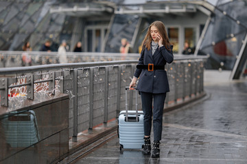 Businesswoman on airport talking on the smartphone while walking with hand luggage in train station or airpot going to boarding gate. Girl using mobile phone and watch for conversation. - Image
