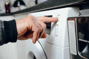 Turning the button on from the washing machine. The man activates the washing machine to do the laundry. The concept of doing laundry, care for clean clothes.
