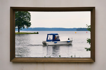 Motorboat on the Schwerin lake in the picture frame. Castle garden in Mecklenburg-Vorpommern.