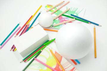 esferas y prisma blancos con pinturas abstractas y lápices de colores desordenados sobre fondo blanco