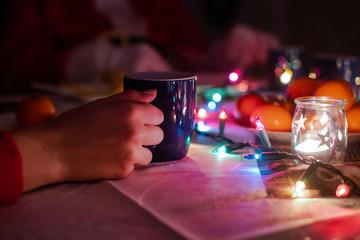 Fototapeta Dłoń trzymająca świąteczny kubek na tle świątecznego stołu