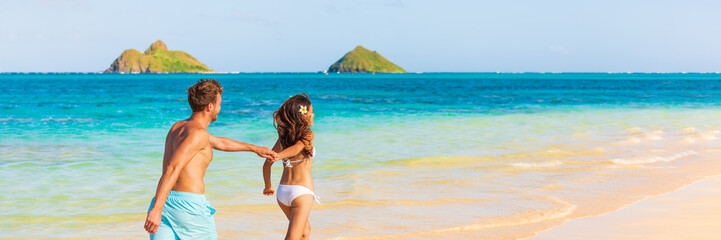 Wall Mural - Beach summer vacation happy young tourists lovers on Hawaii vacation travel. Man and woman holding hands in the Sun. Landscape Panoramic banner people lifestyle.