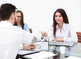 business woman is shaking hands with an employee at a work meeting