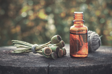 Poppies, poppy flower heads and bottle of infusion. Herbal or homeopathic medicine.