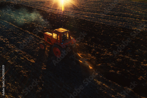 Wall mural Tractor cultivating field at spring, aerial drone view