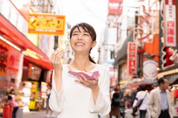 大阪でたこ焼きを食べる女性