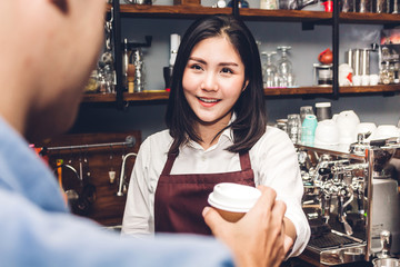 Woman barista behind the counter bar and giving coffee cup to customer at cafe