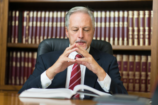 Senior lawyer businessman reading his notes in the home office, thinking, pensive and worried business man